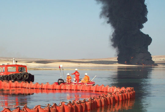 oil spill skimmer with tank on fire in background